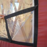 person lifting up the corner of a vinyl yurt window